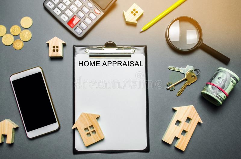 Table with wooden houses, calculator, coins, magnifying glass with the word Home appraisal. The contract for real estate appraisal. Rate the property royalty free stock photography