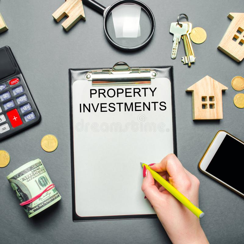 Table with wooden houses, calculator, coins, magnifying glass with the word Property investments. Attracting investment in your stock images