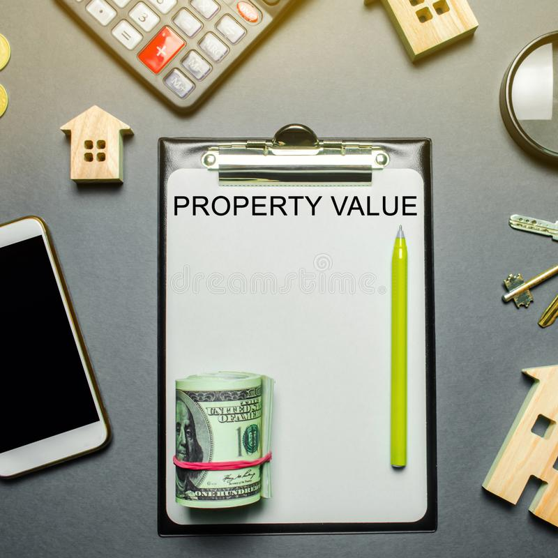 Table with wooden houses, calculator, coins, magnifying glass with the word Property value. The contract for real estate appraisal. Rate the property royalty free stock image