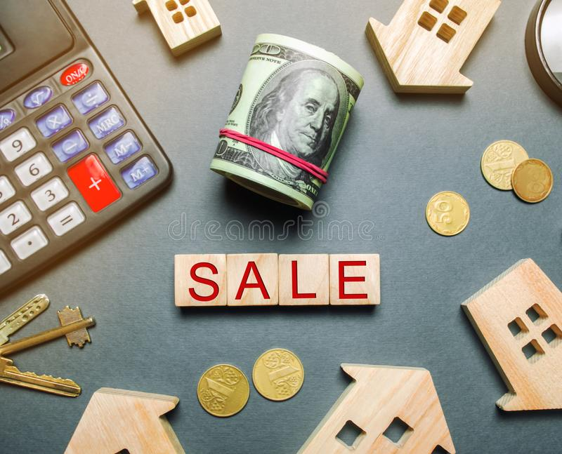 Table with wooden houses, calculator, coins, magnifying glass with the word Sale. Property For Sale. Sell an apartment or house. Housing for sale. Real Estate royalty free stock photo