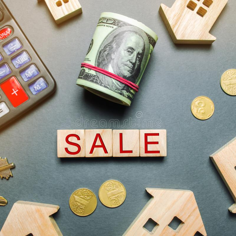 Table with wooden houses, calculator, coins, magnifying glass with the word Sale. Property For Sale. Sell an apartment or house. Housing for sale. Real Estate royalty free stock images
