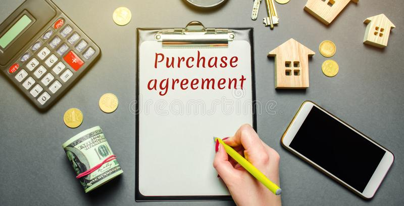 Table with wooden houses, calculator, magnifying glass with the word Purchase agreement. The concept of real estate purchase. Buy stock photo