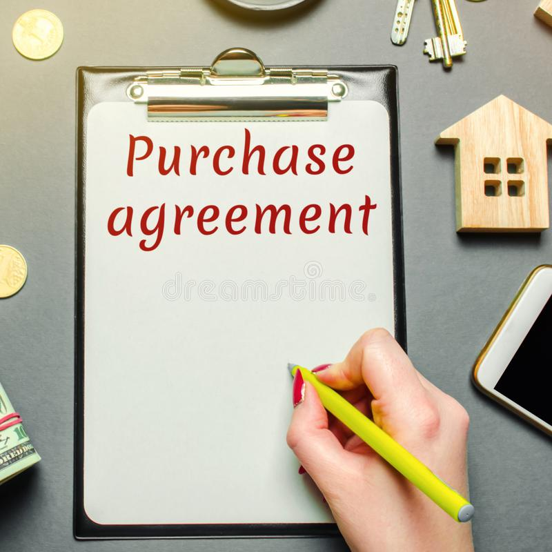 Table with wooden houses, calculator, magnifying glass with the word Purchase agreement. The concept of real estate purchase. Buy. An apartment or house. Buying stock images
