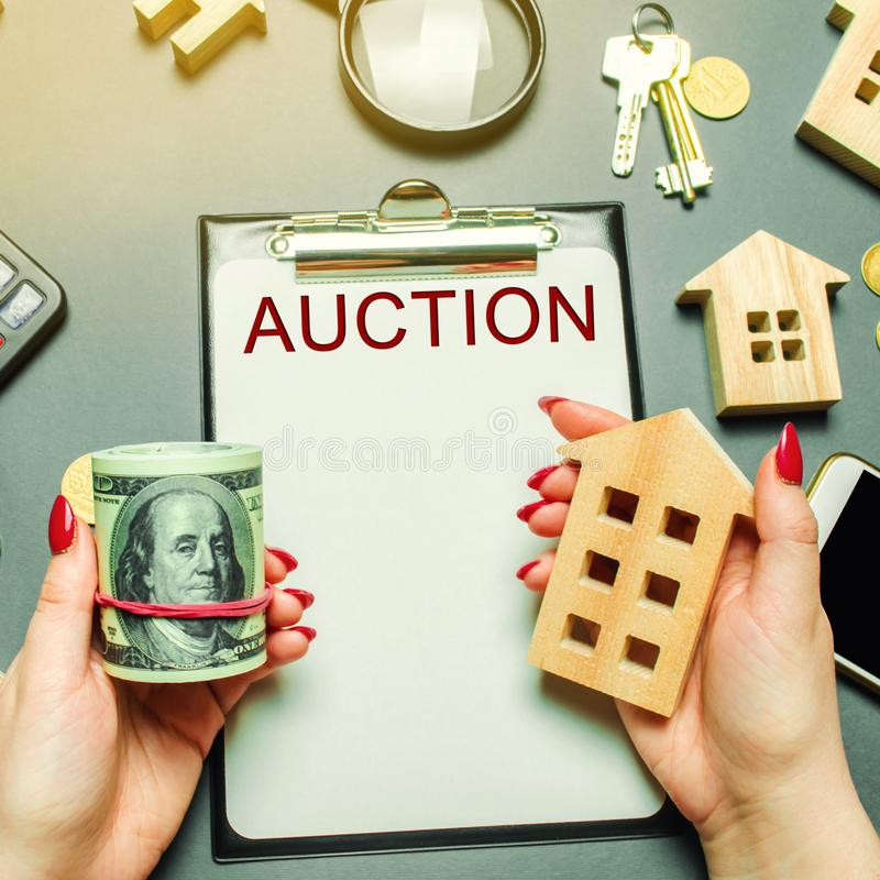 Table with the word Auction. The women auctioneer is holding money in the hands of dollars and a wooden house. Purchase and public. Sale of real estate. Sell or stock images