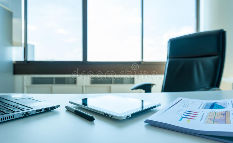 Table work in empty office room with tablet and report stock image