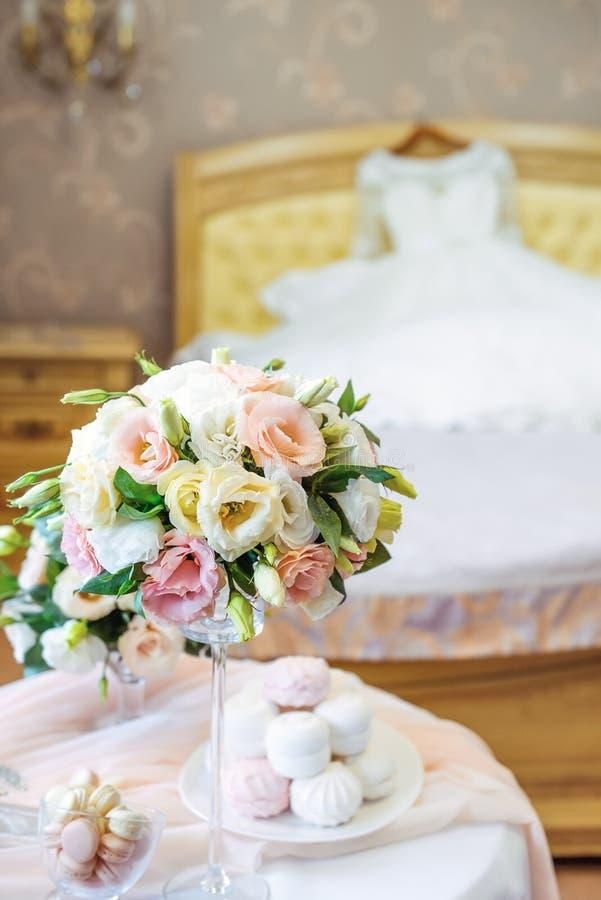 Tableau avec des détails du ` s de jeune mariée : bouquet des fleurs d'eustoma, des bijoux, des parfums et guimauve et des bonbon photos stock