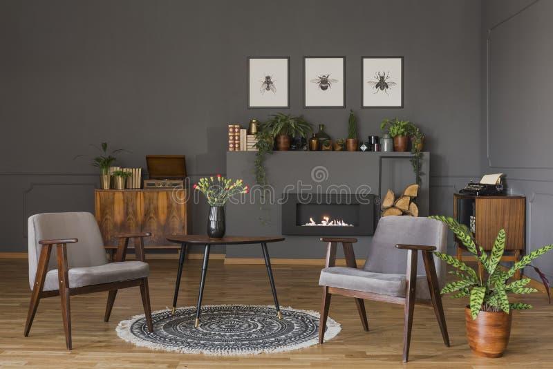 Tableau avec des fleurs sur la couverture entre les fauteuils gris dans la rétro vie photos stock