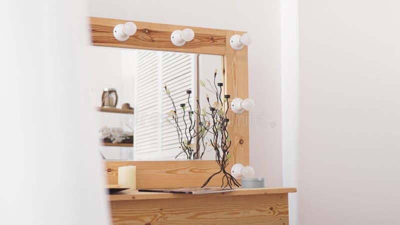 Tableau avec des produits de maquillage et miroir pr?s du mur blanc Int?rieur de vestiaire photographie stock libre de droits