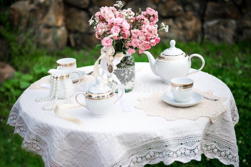 Tableau avec la nappe blanche de dentelle, fleurs roses dans le pot photographie stock libre de droits