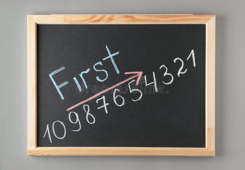 Tableau avec le mot D'ABORD et les nombres sur le fond gris, vue supérieure photos stock