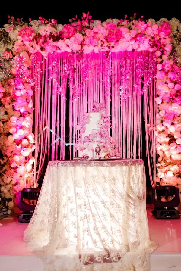 Tableau avec un gâteau l'épousant, les bougies, la lumière et les fleurs Décoration de mariage images stock