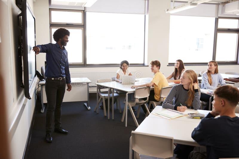 Tableau blanc interactif de Standing Next To de haut maître d'école masculin et leçon de enseignement photos stock