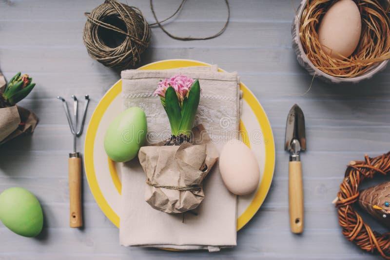 Tableau décoré pour Pâques avec la fleur enveloppée de jacinthe, les outils de jardin et le plat coloré Arrangement à la maison c photographie stock libre de droits