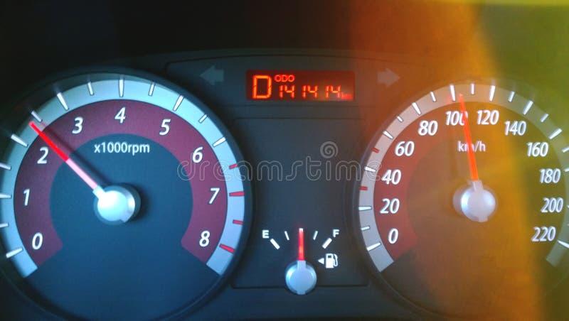 Tableau de bord de voiture tout en conduisant à la grande vitesse - un nombre gentil sur l'odomètre, l'éclat lumineux du soleil photographie stock
