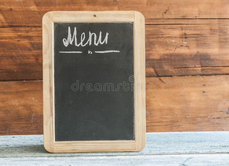 Tableau de menu de restaurant accrochant sur le mur en bois rustique avec la Co image stock