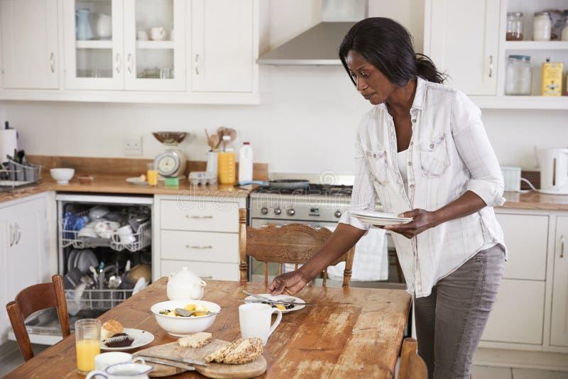 Tableau de petit déjeuner de clairière de femme et lave-vaisselle de chargement images stock