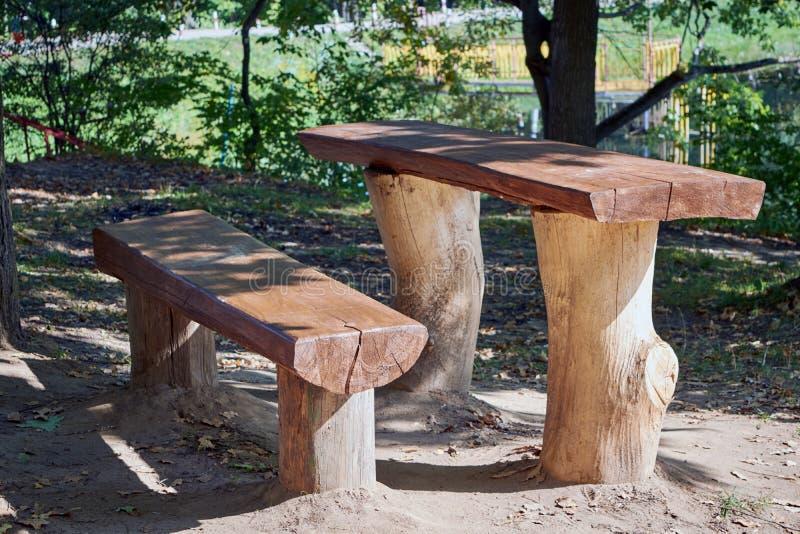 Tableau et banc faits de rondins et conseils en bois en parc sur le lac photos stock