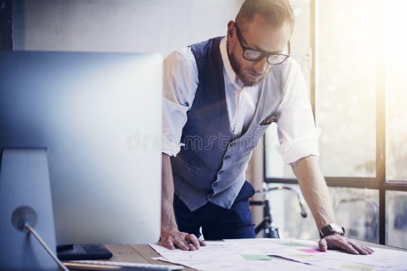 Tableau moderne en bois de lieu de travail d'homme d'affaires de document barbu d'Analyzes Business Plan Jeune homme travaillant  photo stock