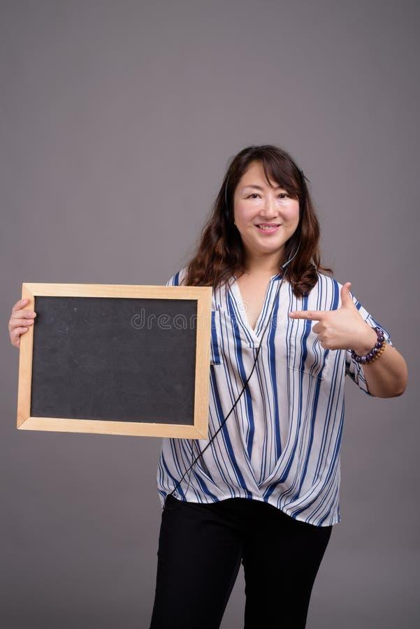 Tableau noir asiatique mûr de participation de femme d'affaires avec l'espace de copie photographie stock libre de droits