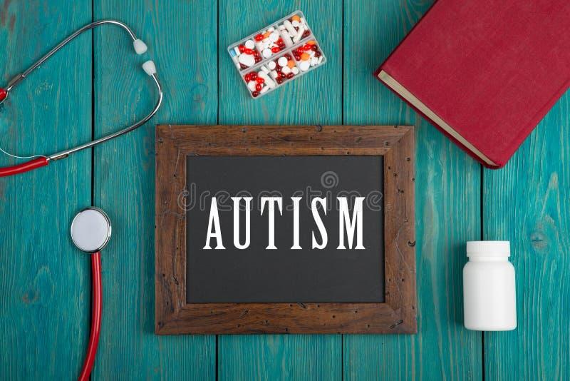 Tableau noir avec le texte et le x22 ; Autism& x22 ; , livre, pilules et stéthoscope sur le fond en bois bleu photos libres de droits