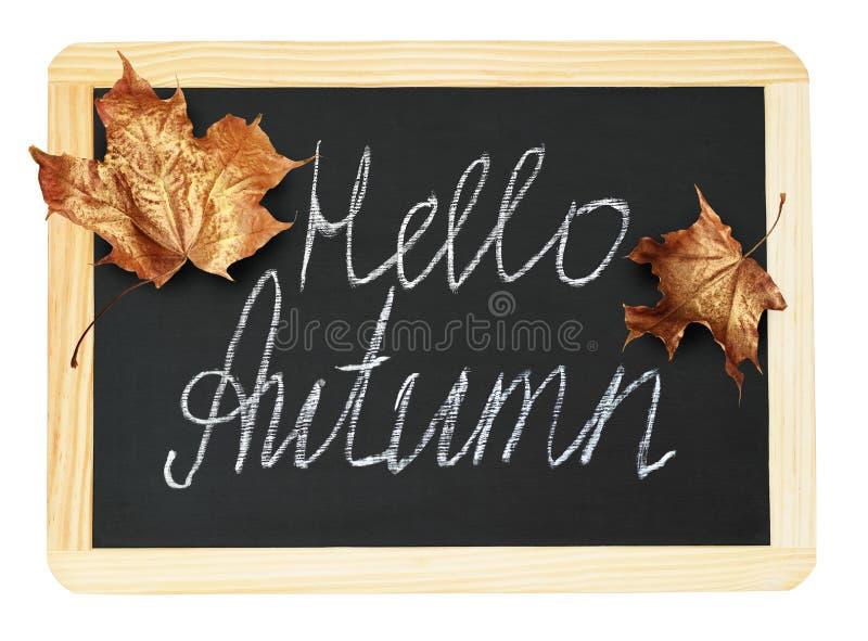 Tableau noir avec les feuilles d'or et l'inscription d'érable de l'automne de bonjour image stock