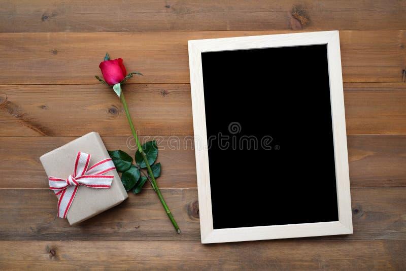 Tableau noir, boîte-cadeau et rose vides de rouge sur le fond en bois photos stock