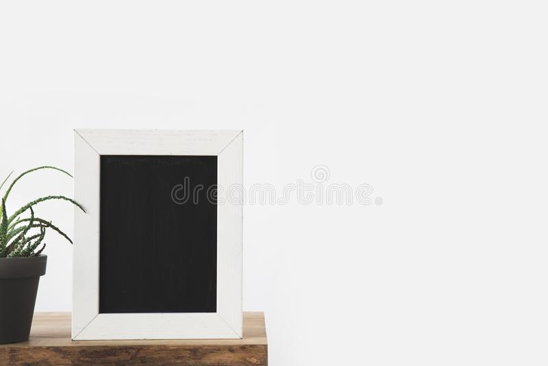tableau noir dans le cadre et usine sur la table sur le blanc image stock