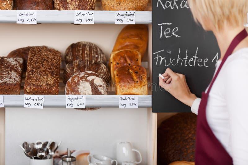 Tableau noir de Writing Menu On de serveuse dans la boulangerie images libres de droits