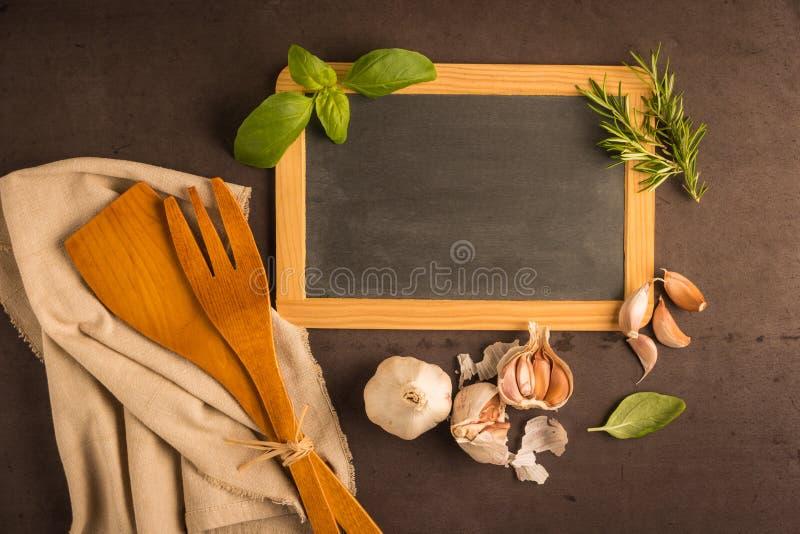 Tableau noir pour votre texte, herbes fraîches de jardin sur la table en pierre bas photos libres de droits