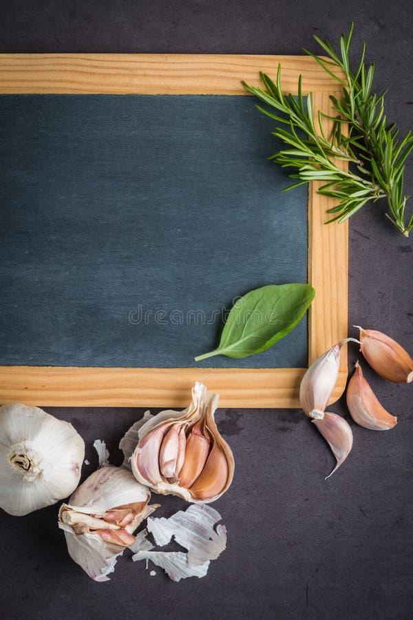 Tableau noir pour votre texte, herbes fraîches de jardin sur la table en pierre bas image libre de droits