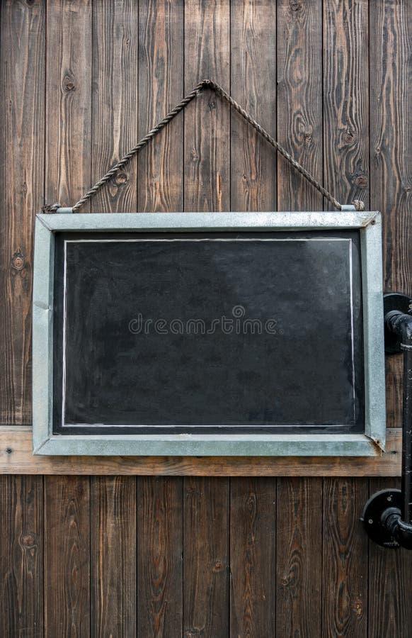 Tableau noir rustique vide accrochant sur la porte en bois photos stock