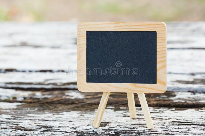 Tableau noir vide sur la table en bois image stock