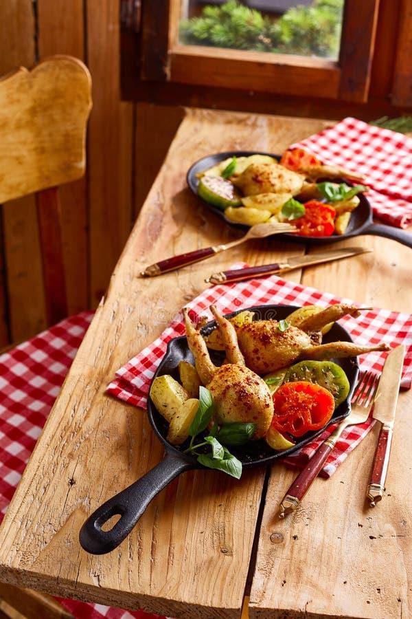 Tableau pour deux avec des portions des cailles de r?ti photos stock