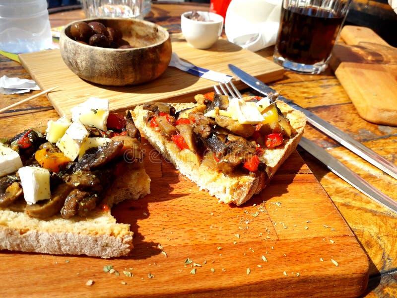 Tableau servi avec les morceaux de pain délicieux complétés avec des légumes et une cuvette avec des olives photo libre de droits