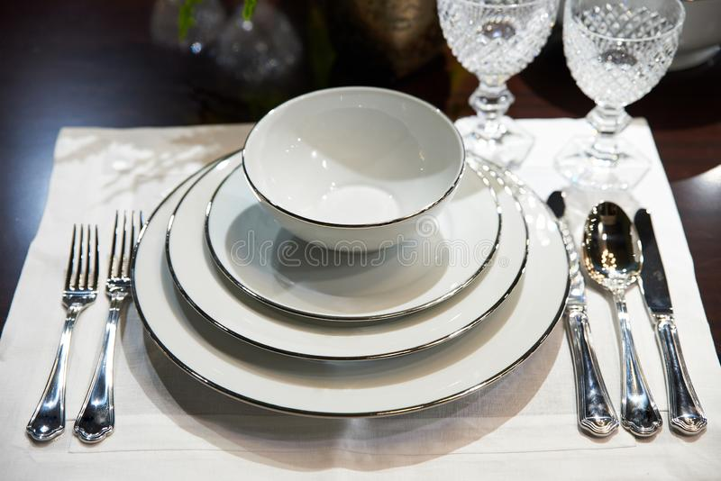 Tableau servi avec les plats et les verres cristal blancs chers image stock