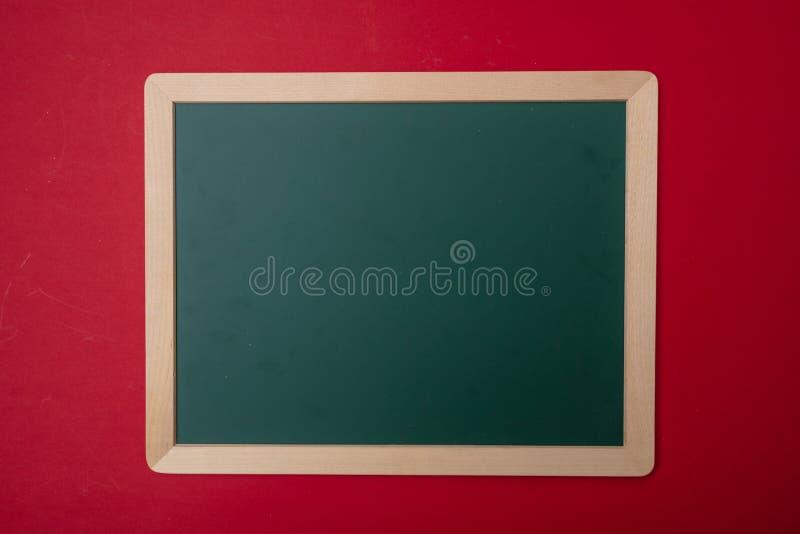 Tableau vide vide vert avec le cadre en bois, fond rouge de mur, l'espace de copie photos stock