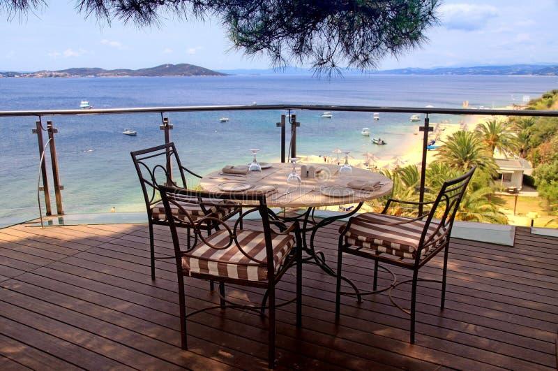Tablecloth, żelaz krzesła i denny widok, Grecja. zdjęcia royalty free