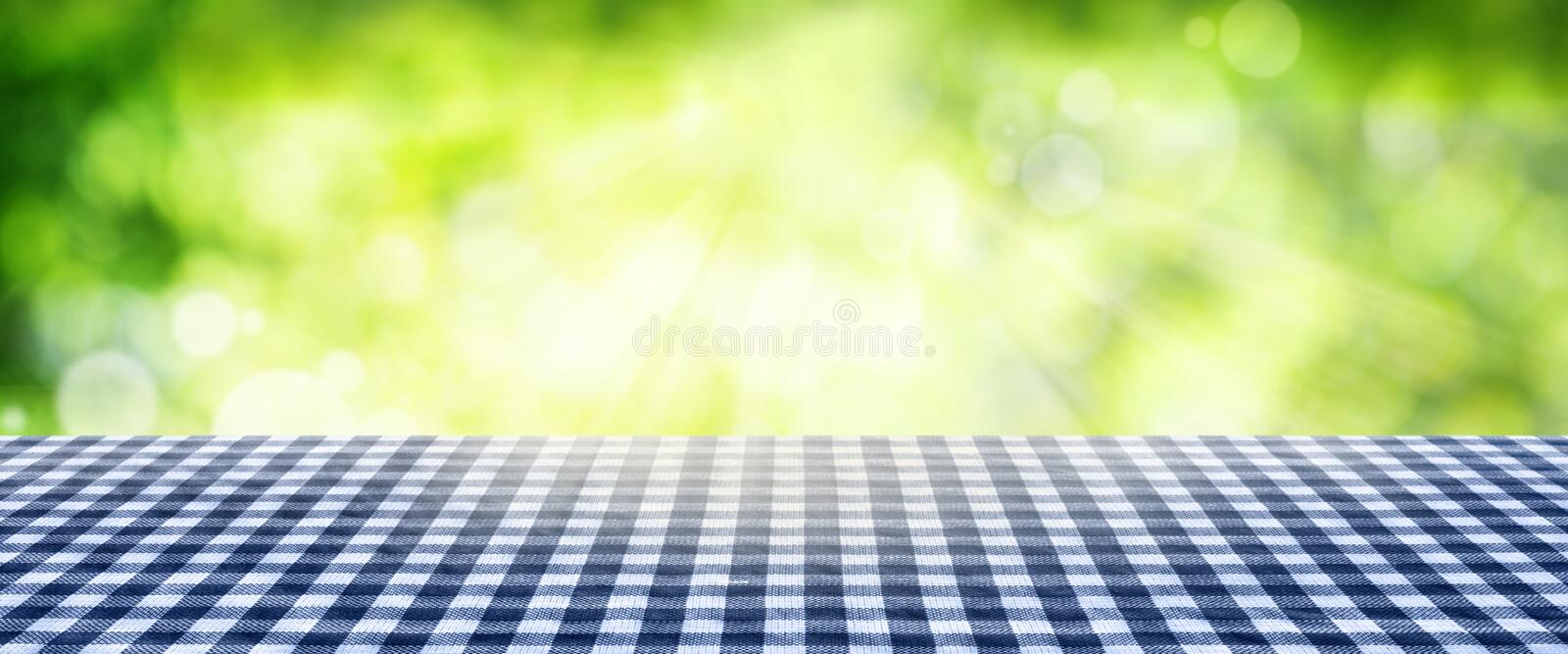 Tablecloth with spring background. Tablecloth blue checkered in front of sunny green spring background for a bavarian decoration stock photos
