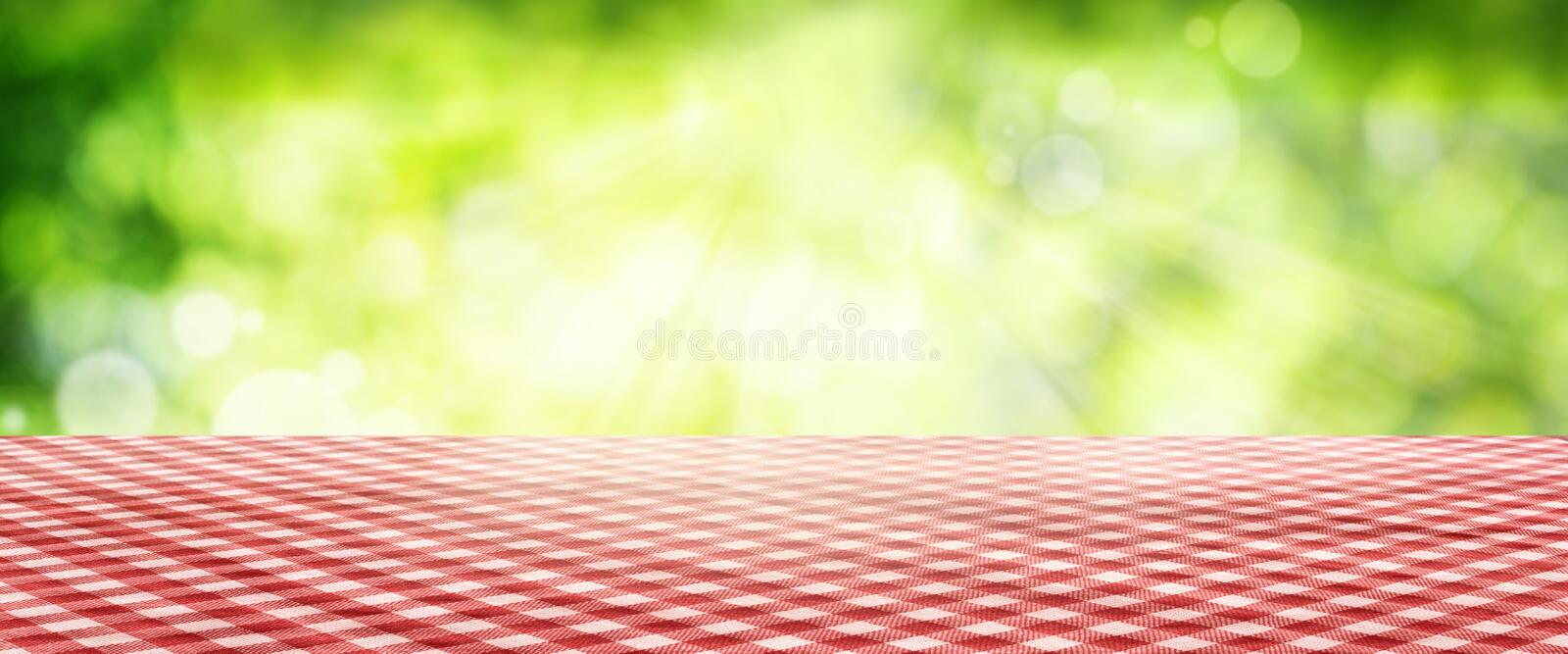 Tablecloth with spring background. Luminous green spring background with a red checkered Tablecloth for a bavarian concept royalty free stock images