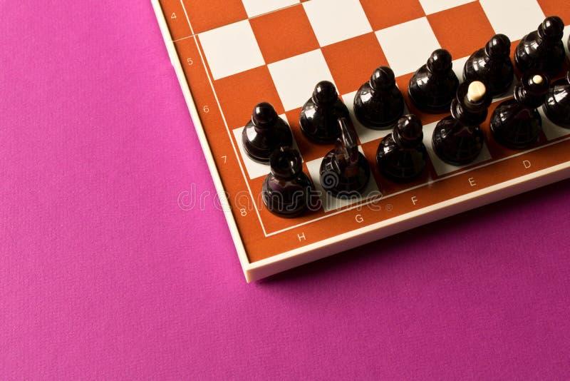 Tablero con ajedrez negro en fondo púrpura El concepto de fotografía de archivo