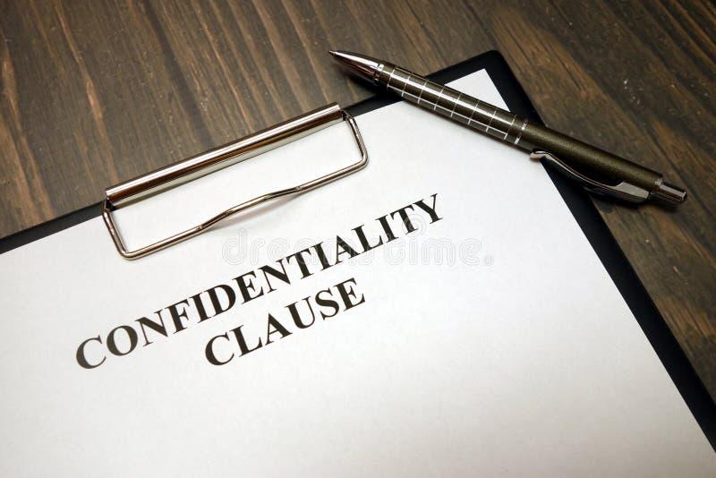 Tablero con cláusula de la confidencialidad y pluma en el escritorio fotografía de archivo libre de regalías