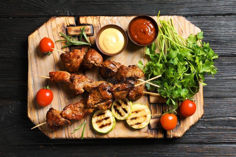 Tablero con la carne, la guarnición y las salsas asadas a la parilla en fondo de madera foto de archivo libre de regalías