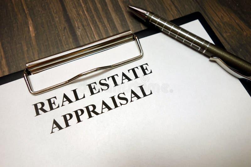 Tablero con la maqueta de la valoración de propiedades inmobiliarias y pluma en el escritorio imagenes de archivo