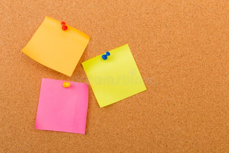 Tablero con las notas en blanco coloreadas fijadas - imagen del corcho fotografía de archivo libre de regalías