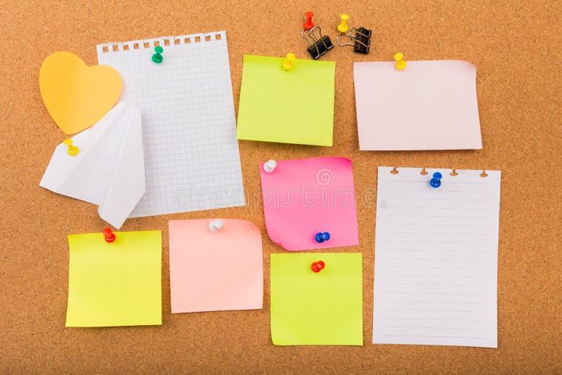 Tablero con las notas en blanco coloreadas fijadas - imagen del corcho fotos de archivo