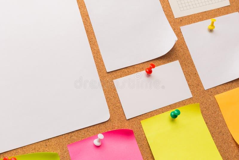 Tablero con las notas en blanco coloreadas fijadas - imagen del corcho imagen de archivo libre de regalías
