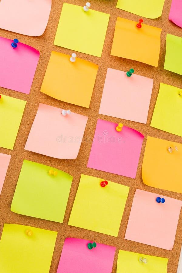 Tablero con las notas en blanco coloreadas fijadas - imagen del corcho imágenes de archivo libres de regalías
