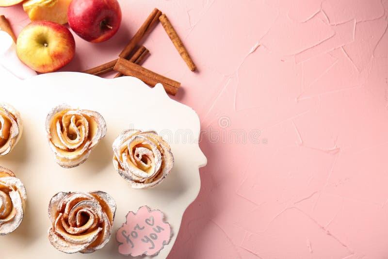 Tablero con las rosas sabrosas de la manzana de la pasta de hojaldre en la tabla foto de archivo libre de regalías
