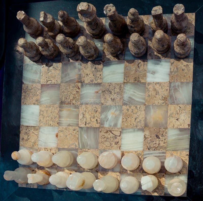 Tablero de ajedrez con los pedazos de ajedrez de mármol imagenes de archivo