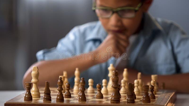 Tablero de ajedrez en la tabla delante del escolar que piensa en el próximo paso, torneo foto de archivo